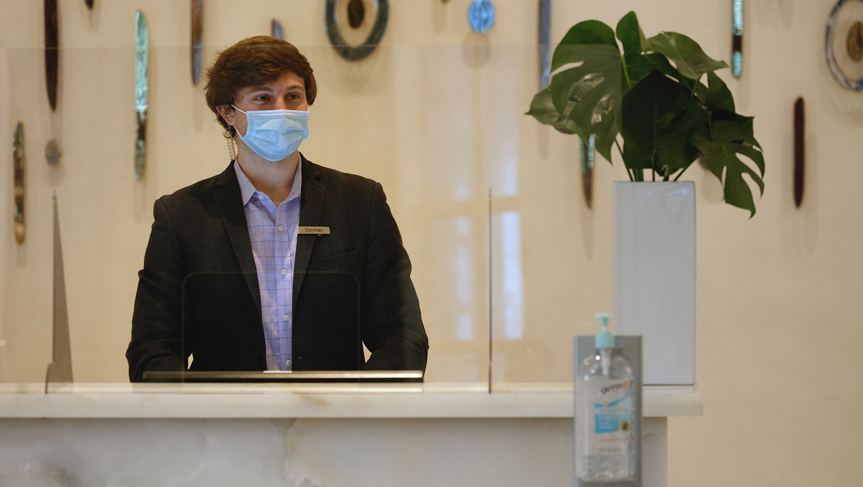desk clerk with mask on in socially distant lobby